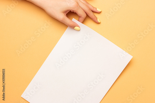 Pinturas sobre lienzo  Beautiful female hands are holding blank A4 form on a bright yellow background