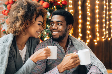 Young couple drinking coffee and enjoying Christmas morning