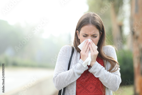 Photo Ill woman blowing using tissue walking in a park with fog