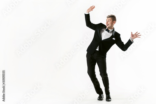 Valokuva Portrait of young smiling handsome show man in tuxedo stylish black suit, studio shot dancing at white background