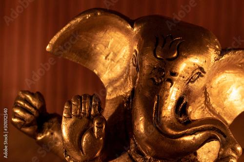Canvastavla Extreme close up of  golden ganesha murti figure with wooden background illuminated by candlelight