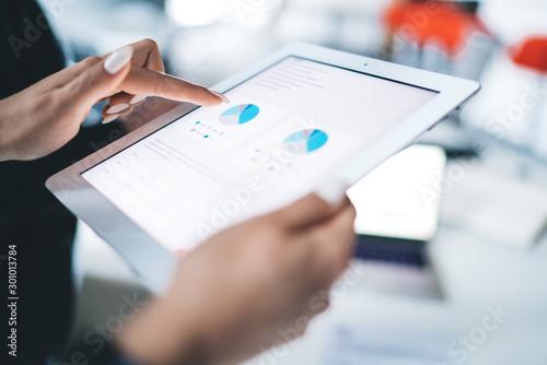 Fotografia Crop hands browsing tablet in office