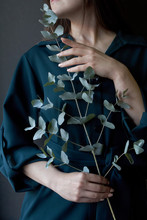 Portrait Of A Girl In A Green Dress Holding A Eucalyptus Branch On A Dark Background, Selective Focus