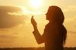 Leinwanddruck Bild - Beautiful Muslim woman praying outdoors at sunset