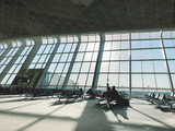 Fototapeta Perspektywa 3d - Light waiting area of airport with big windows.Interior of modern waiting room of airport with huge glass windows and rows of seats in sunlight
