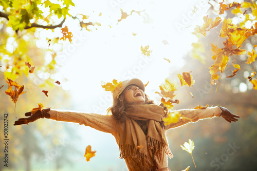 Cadres-photo bureau Attraction parc woman enjoying autumn and catching falling yellow leaves
