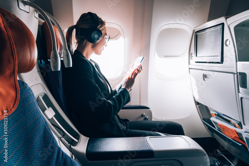 Caucasian female airplane passenger reading received email via mobile phone during trip connected to wireless internet on board, successful young woman travelling in first business class. Wifi hotspot
