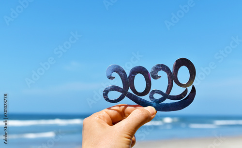 Obraz Happy New Year creative concept, hand holding 2020 text against blue sky and beach blur defocused background. - fototapety do salonu