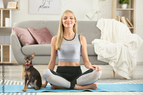 Cuadros en Lienzo Beautiful young woman with cute toy terrier dog practicing yoga at home
