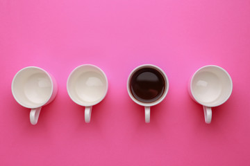 One cup of coffee among empty ones on color background. Concept of uniqueness