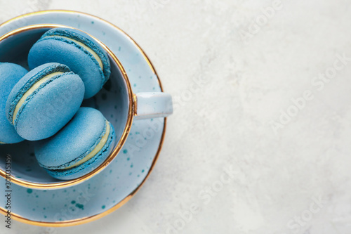 Cup with tasty macarons on white background Tableau sur Toile