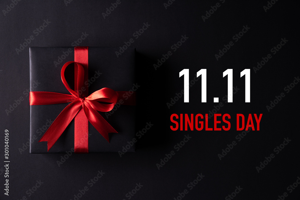 Fototapeta Online shopping of China, 11.11 singles day sale concept. Top view of black christmas boxes with red ribbon on black background with copy space for text 11.11 singles day sale.