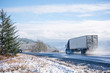 canvas print picture - Two big rigs semi trucks with semi trailers go towards each other on the winter wet road with melting snow