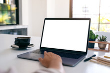 Mockup Image Of A Hand Using And Touching On Laptop Touchpad With Blank White Desktop Screen With Coffee Cup On Wooden Table