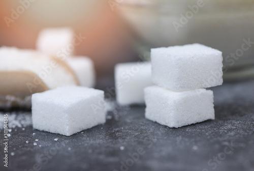 Obraz na plátně  Close up of white sugar - Sugar cubes on table background selective focus