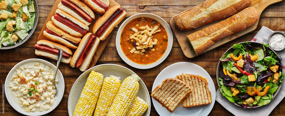 Fototapeta table top meal with hot dogs, grilled cheese, soup and salad in flat lay composition
