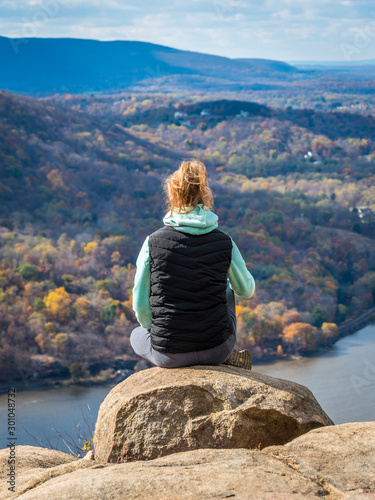 Teenage girl sits on the cliff of Breakneck Ridge trail Wallpaper Mural