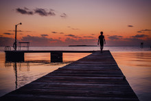 Getting Away From It All. Silhouette Of A Boy Walking Out On A Dock In The Florida Keys. Watching The Sunset Over The Horizon With The Ocean In Front Of Him.