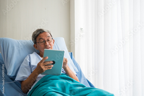 Papel de parede Happy elderly patient sitting on bed and making video call with tablet at hospital