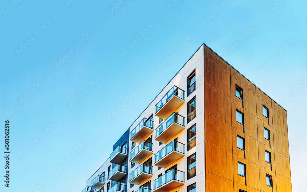 Fototapeta Part of Modern residential apartment with flat building exterior. Detail of New luxury house and home complex. Fragment of City Real estate property and condo architecture. Copy space. Blue sky