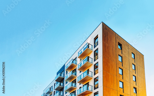 Obraz Part of Modern residential apartment with flat building exterior. Detail of New luxury house and home complex. Fragment of City Real estate property and condo architecture. Copy space. Blue sky - fototapety do salonu