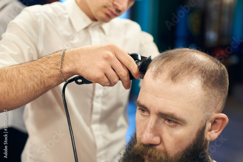 Electric trimmer machine in skillful barber's hand, cutting short hair on client's head Canvas Print