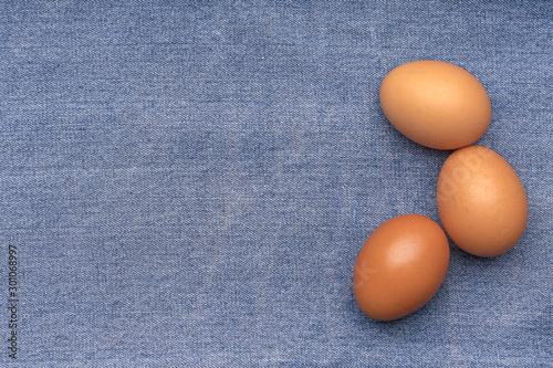 Brown chicken eggs on a blue denim.