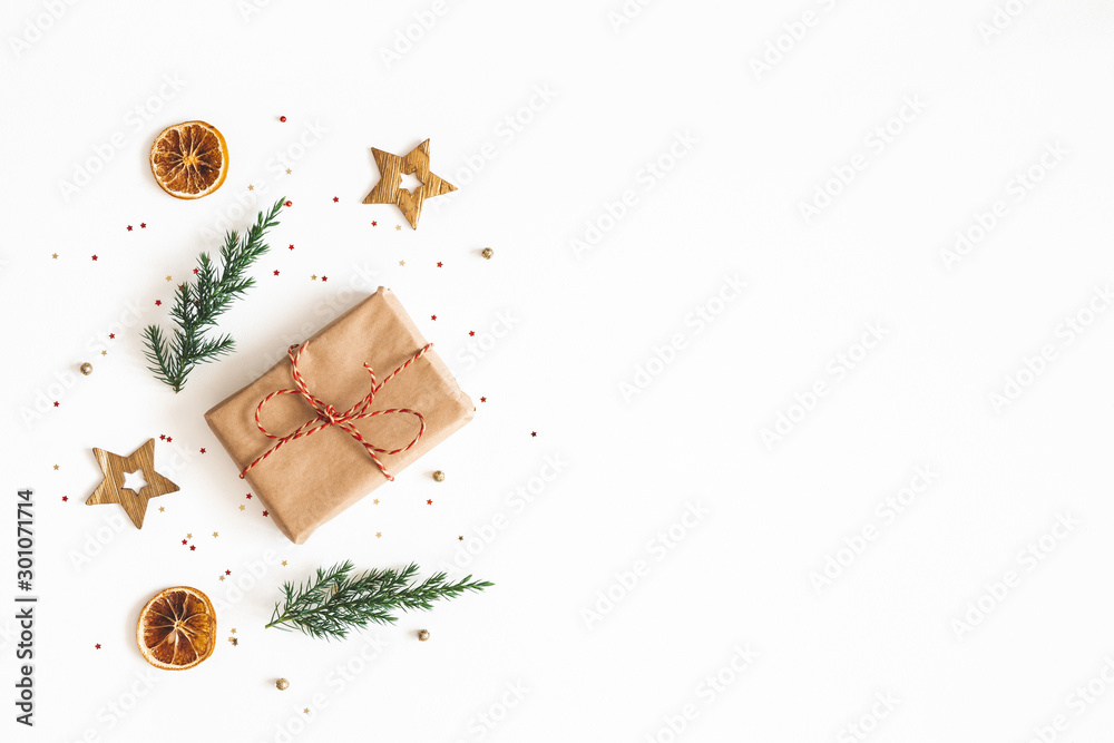 Fototapeta Christmas composition. Gift box, fir tree branches, golden decorations on white background. Christmas, winter, new year concept. Flat lay, top view, copy space