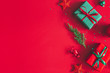 Leinwanddruck Bild - Christmas composition. Gift box, christmas decorations on red background. Flat lay, top view, copy space