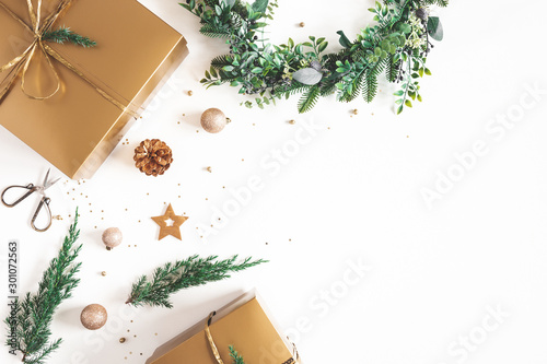 Christmas composition. Gift box, wreath, golden decoration on white background. Christmas, winter, new year concept. Flat lay, top view