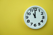 White Round Clock Showing Eleven O'clock On Yellow Background