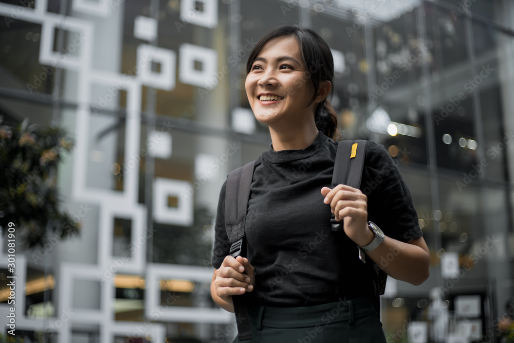Fototapeta Portrait of happy asian woman in the city