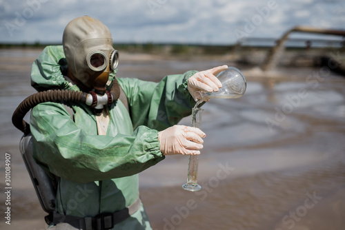 Fotomural  A male environmentalist in a green protective suit and gas mask takes a sample of water