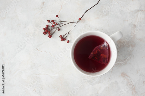 Fruity tea in tea pyramid bag in white cup and red berries on marble background. Cozy winter mood, top view