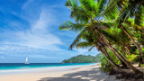 Tropical white sand beach with coconut palm trees and a sailing boat in turquoise sea on Seychelles tropical island.