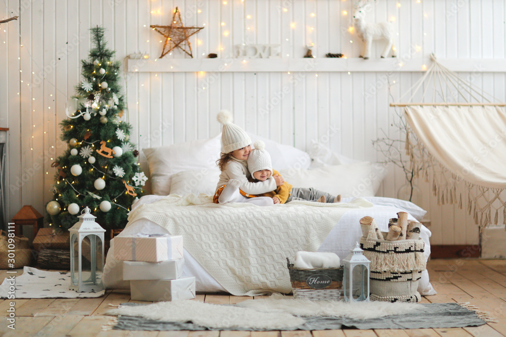 Fototapety, obrazy: sisters are hugging on bed in Christmas interior