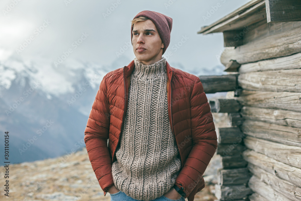 Fototapeta Handsome male model wearing warm sweater and winter coat over mountains with snow