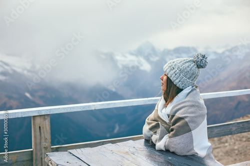Pinturas sobre lienzo  Teenage girl wrapped in plaid blanket sitting by table on mountain top