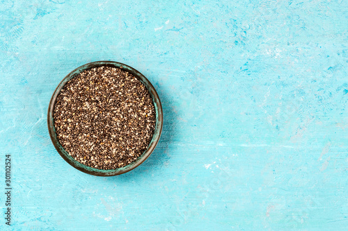 Chia seeds in a bowl, shot from the top on a blue background with a place for text