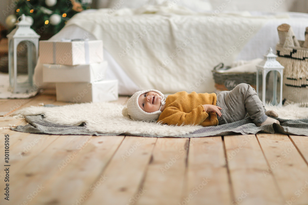 Fototapeta Funny baby in hat and sweater lies near the bed