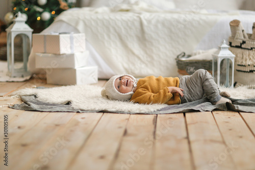 Funny baby in hat and sweater lies near the bed Fototapet