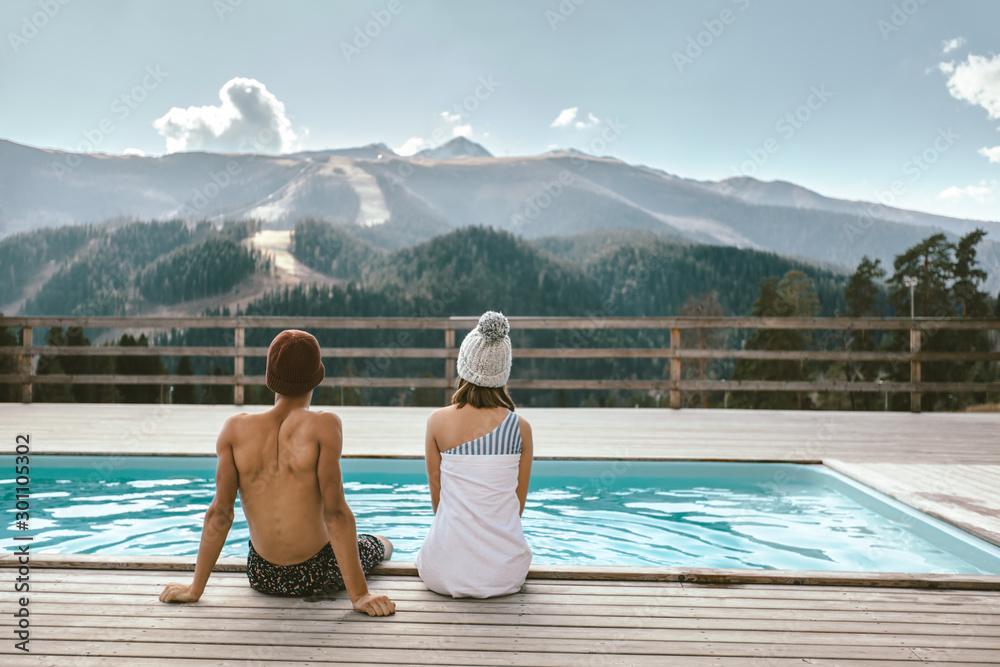 Fototapeta Two people spending vacation in swimming pool with mountain landscape