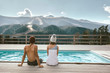 canvas print picture - Two people spending vacation in swimming pool with mountain landscape