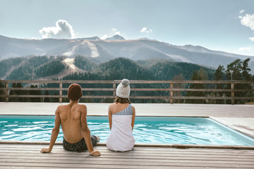 FototapetaTwo people spending vacation in swimming pool with mountain landscape