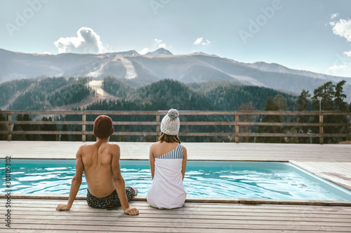 Two people spending vacation in swimming pool with mountain landscape - 301105302