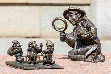 Wroclaw, Poland dwarf gnomes sculpture with magnifying glass in downtown of famous polish city