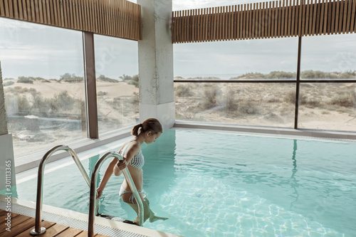 Obraz Girl relaxing in luxury swimming pool in modern hotel - fototapety do salonu