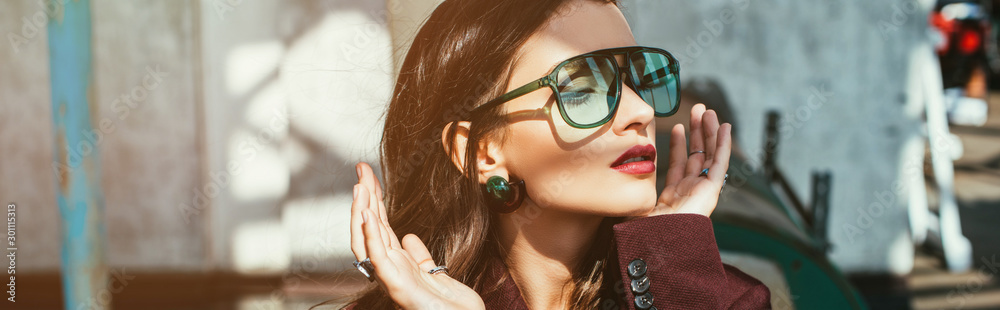 Fototapeta fashionable woman posing in trendy burgundy suit and sunglasses on urban roof