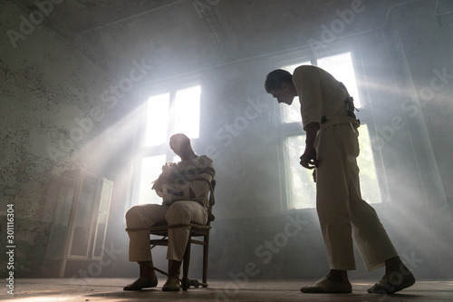 Photo A crazy man in a straitjacket is tied to a chair in an abandoned old clinic and