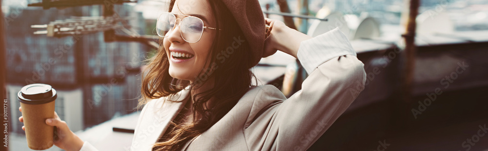 Fototapeta smiling fashionable girl in beige suit and beret posing on roof with coffee to go